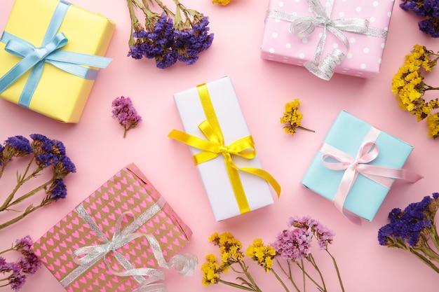 Подарочная или подарочная коробка и цветок. пастельный цвет. открытка. вид сверху