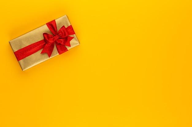 Подарочная или подарочная коробка на цветном столе. плоская композиция для дня рождения, дня матери или свадьбы.