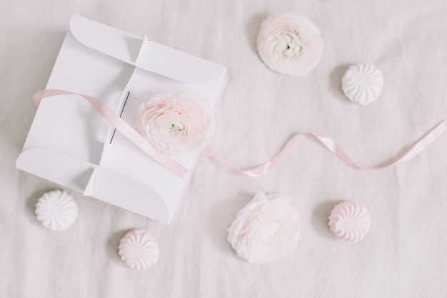 白い表面の上面図にピンクのリボンと花のギフトまたはプレゼントボックス Premium写真