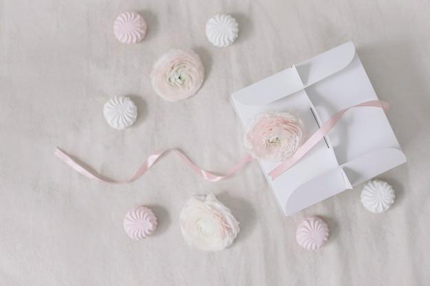 白い表面の上面図にピンクのリボンと花のギフトまたはプレゼントボックス