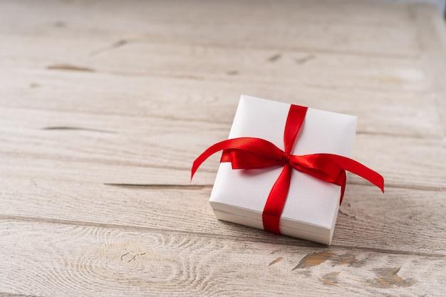Подарочная или настоящая коробка с красным бантом на деревянном фоне. пастельные тона, место для текста и дизайна
