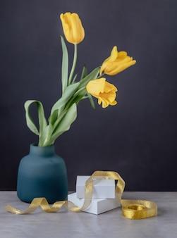 Подарочная или настоящая коробка, завернутая в белую бумагу и цветы тюльпана на сером столе. золотая лента