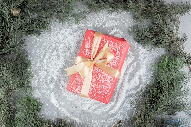 Gift package sitting on coconut powder amidst pine branches on marble table.