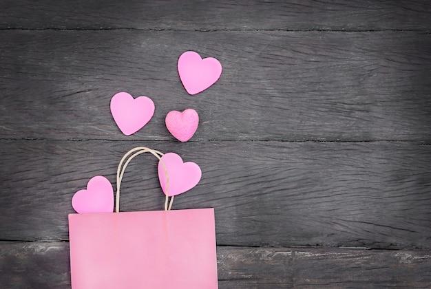 나무 배경에 마음으로 선물 패키지입니다. 복사 공간 핑크 하트 핑크 가방