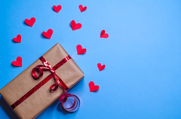 Gift in package with red ribbon and hearts in recognition of love on blue background for new year, christmas, valentines day, birthday.