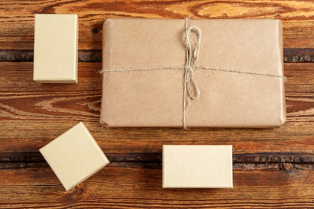 Gift packed in eco-friendly biodegradable cardboard on dark old wooden background with blank space for text