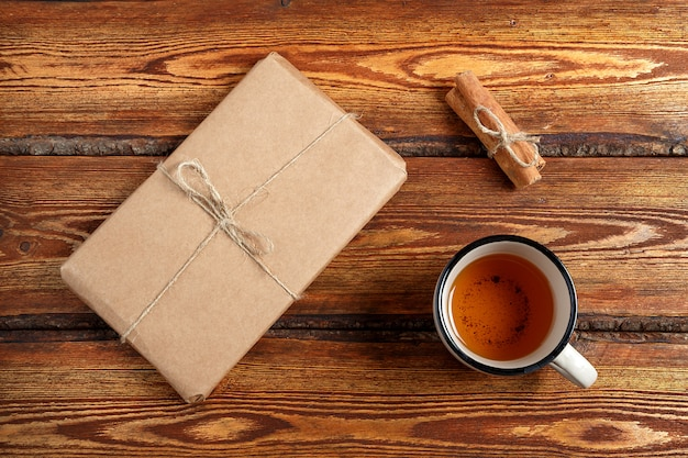 Gift packed in eco-friendly biodegradable cardboard and a glass of tea on a dark old wooden background with a blank space for text