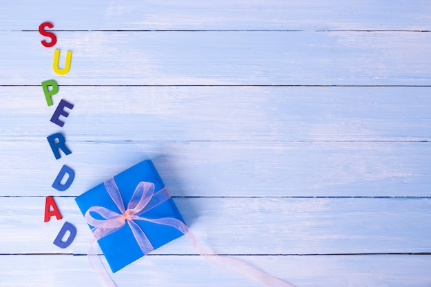 Gift on pastel blue wooden background with text