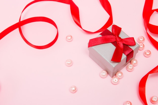 Gift on a pink background with beads and a red ribbon.