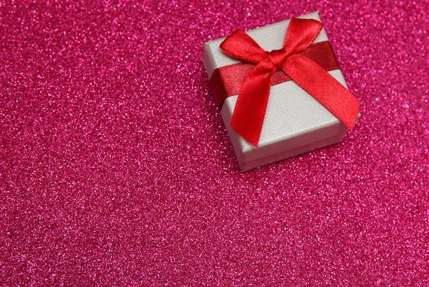 Подарочная розовая коробка на сверкающем розовом фоне.