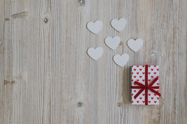 Gift of polka dots with red bow with paper hearts on a wooden table