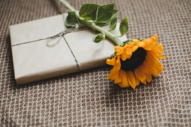 Gift or present box in craft paper and fresh sunflower