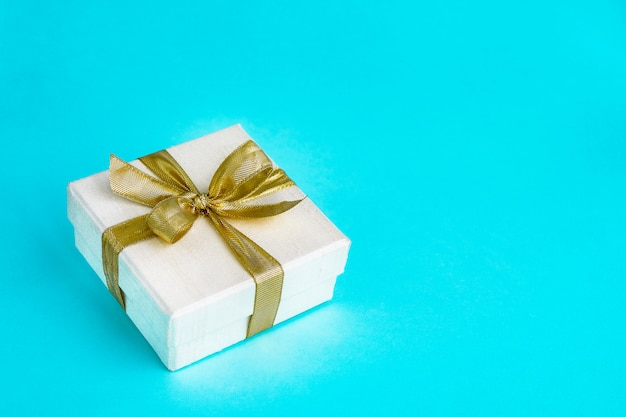 Gift or present box decorated with golden ribbon on blue background. top view, copyspace. birthday, mothers day, wedding, valentine day concept.