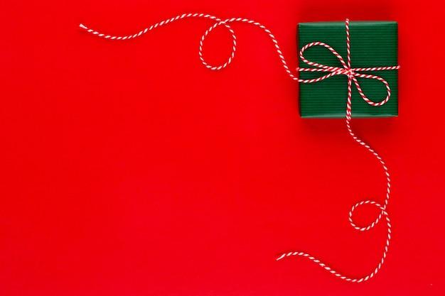 Подарочная коробка на красном фоне вид сверху. плоская композиция на день рождения, день матери или свадьбу.
