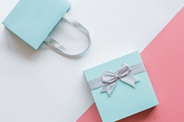 Gift or present box on pink table top view