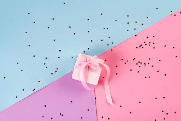 Gift or present box and sequins on pink table top view. flat lay. birthday, wedding or christmas concept.