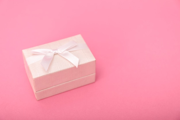 Gift or present box and stars confetti on pink table top view.