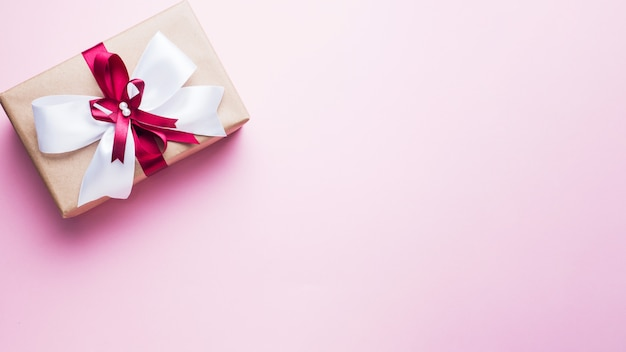 Gift or present box with a big bow on a pink table top view. flatlay composition for christmas birthday, mother day or wedding.