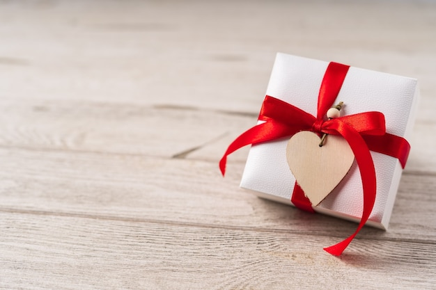 Gift or present box with red bow and heart on wooden background