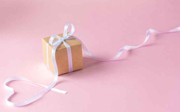 Gift or present box with white ribbon on pink background.