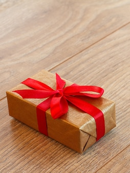 Gift or present box wrapped in kraft paper with red ribbon on wooden boards. top view with copy space.