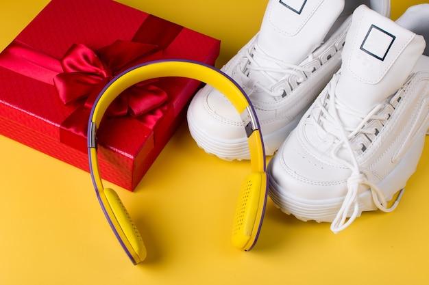 Подарочная красная коробка белых брендовых кроссовок и наушников. на желтом фоне