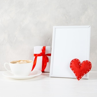 A gift, red heart, morning coffee against the of a light wall, concept, a postcard for valentine's day.