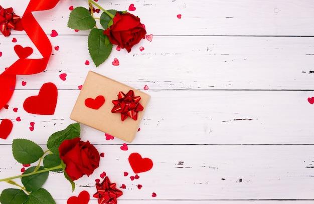 ギフト、白い木製の背景、上面図にバラと赤のハート。コピースペース、バレンタインデーのコンセプト。