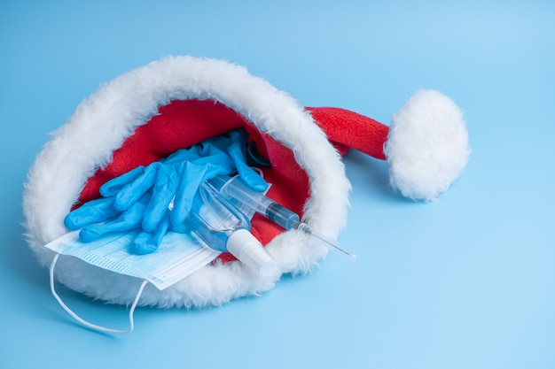 Gift set for christmas and new years 2021 holidays. a hygienic set of a medical mask, gloves, a disinfectant and a syringe with a vaccine and a coronavirus chip in a santa claus hat. vaccination 2021