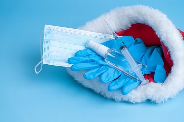 2021년 크리스마스와 새해 연휴를 위한 선물 세트. 위생적인 의료용 마스크, 장갑, 소독제, 백신이 있는 주사기, 산타클로스 모자에 코로나바이러스 칩이 들어 있습니다. 예방 접종 2021.