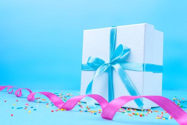 ギフト、サテンブルーのリボンで結ばれた小さな箱。ギフトのコンセプト。愛する人への驚きと贈り物、休日のお祝い、贈り物
