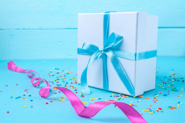 Gift, small box tied with a satin blue ribbon. gift concept. surprises and gifts for loved ones, congratulations on holidays, give gifts