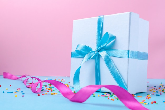 Gift, small box tied with a satin blue ribbon. gift concept. surprises and gifts for loved ones, congratulations on holidays, give gifts.