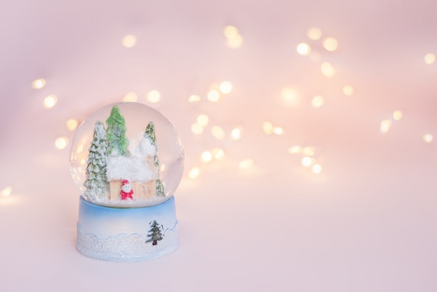 Gift snow globe souvenir on a light pink background with christmas lights