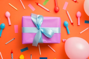 Gift surrounded by birthday elements