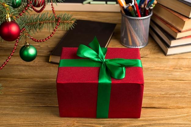 책, 주최자 및 칠판 선물 교사의 테이블. 크리스마스와 새해의 개념.