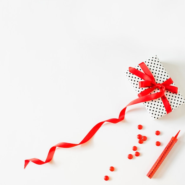 Gift tied with red ribbon near candies and sparkler candle on white background