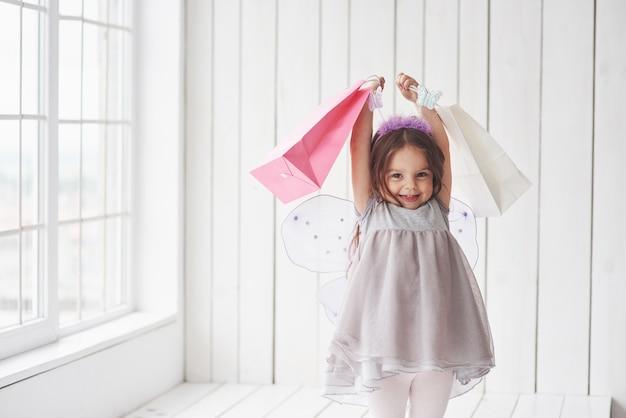 Время подарка. красивая маленькая девочка в костюме феи весело позирует для фотографий.