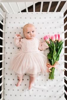 Подарок маме на праздник. новорожденная девочка рука букет цветов розовых тюльпанов на кровати.