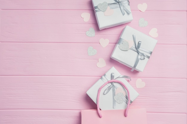 Gift white boxes with silver satin ribbon on pink packages and confetti in form of heart