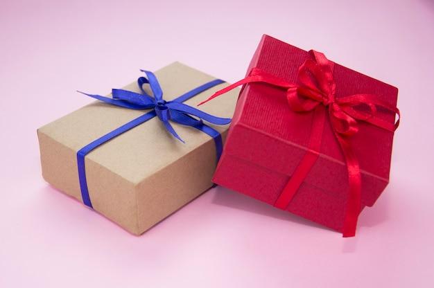 분홍색 배경에 파란색과 빨간색 리본이 달린 선물. 선물 포장. 테이프가 있는 상자.
