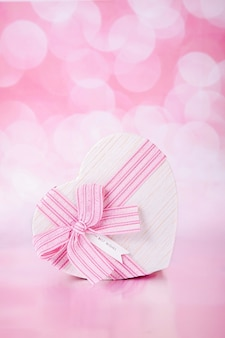 Bokeh와 분홍색 배경에 심장의 형태로 활과 선물