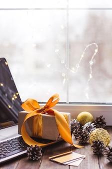 Подарок с золотой лентой и ноутбуком и банковской картой на деревянном столе рождественские интернет-магазины