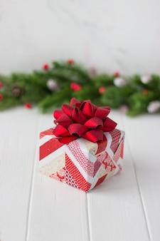 Подарок с красным бантом на фоне еловых веток с шишками и красными ягодами на белом столе
