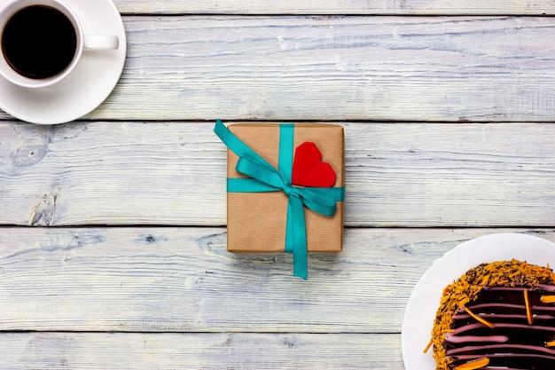 Подарок с небольшой запиской в виде красного сердечка, чашки кофе и шоколадного торта на светлом столе.