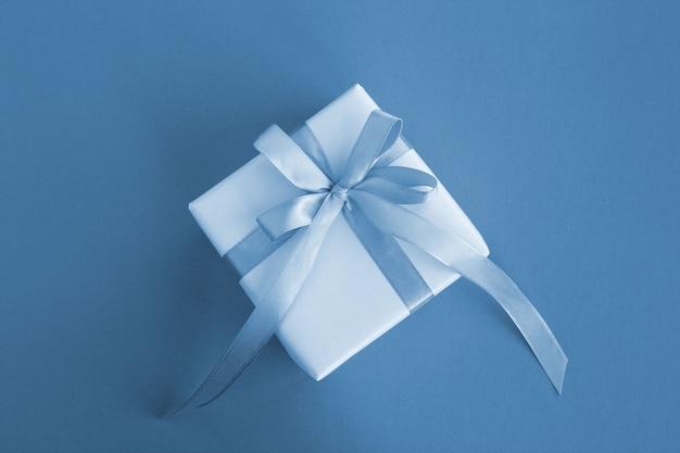 파란색 배경의 중앙에 파란색 활과 선물. 평면도. 공간을 복사하십시오.