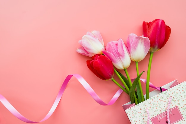 Gift with bouquet of flowers in bag on pink background