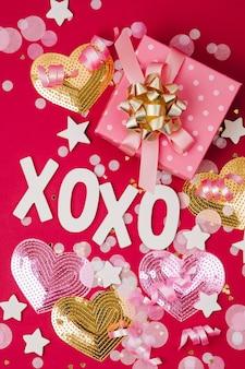 Подарок с конфетти, бантами и бумажными украшениями. день святого валентина или тема концепции вечеринки по случаю дня рождения. плоская планировка, вид сверху