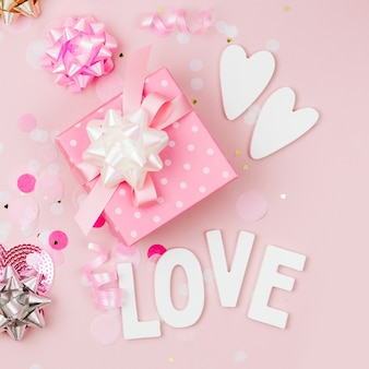 Gift with confetti, bows and paper decorations. valentines day or birthday party concept theme. flat lay, top view
