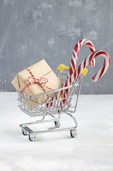 Gift with craft paper, candy cane and red and white twisted cord in small shopping cart.